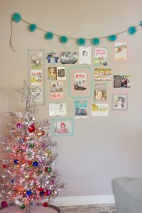 A simple gallery wall-type display is made festive with garland and other decorations